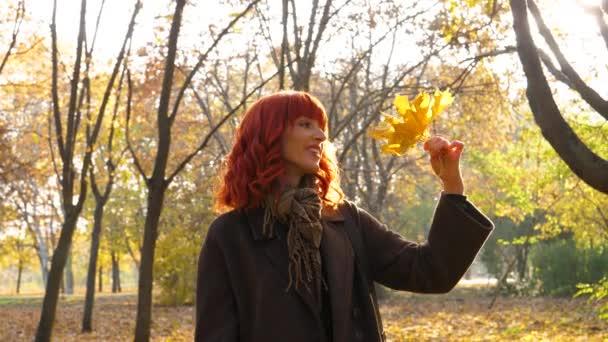 dívka s rudými vlasy v podzimním parku