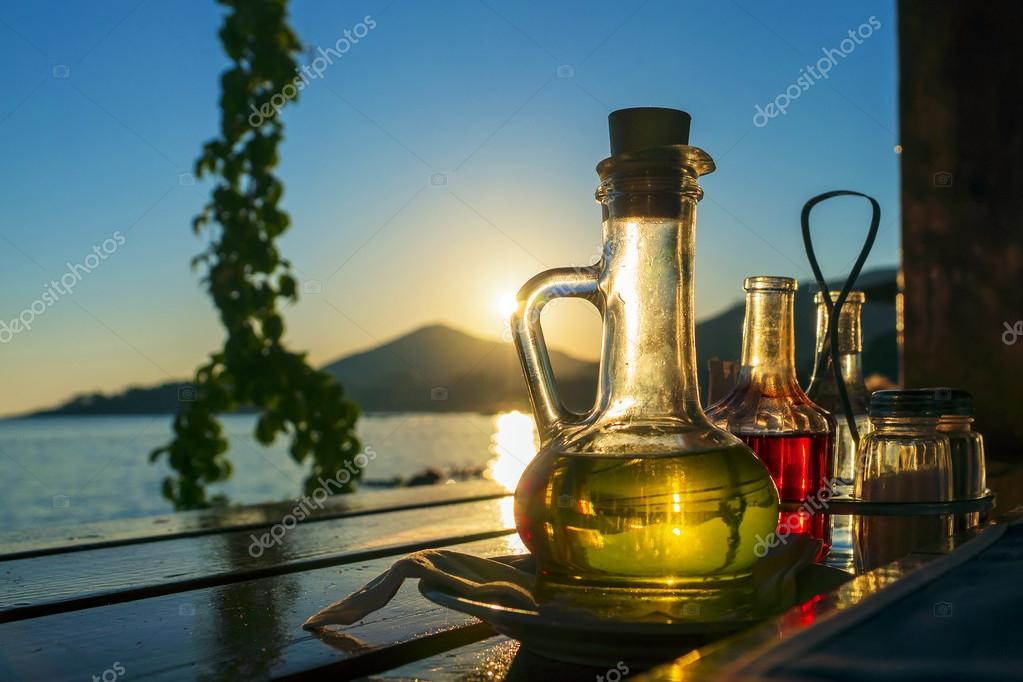 bottle with olive oil on a background of sea sunset