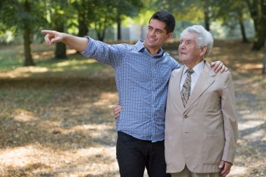 Young man showing something grandfather