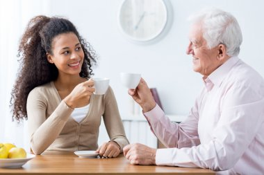 Intergenerational discussion with cup of coffee