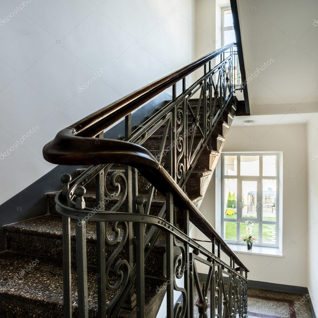 Garde Corps Metal Design staircase with old, decorative railing and white walls