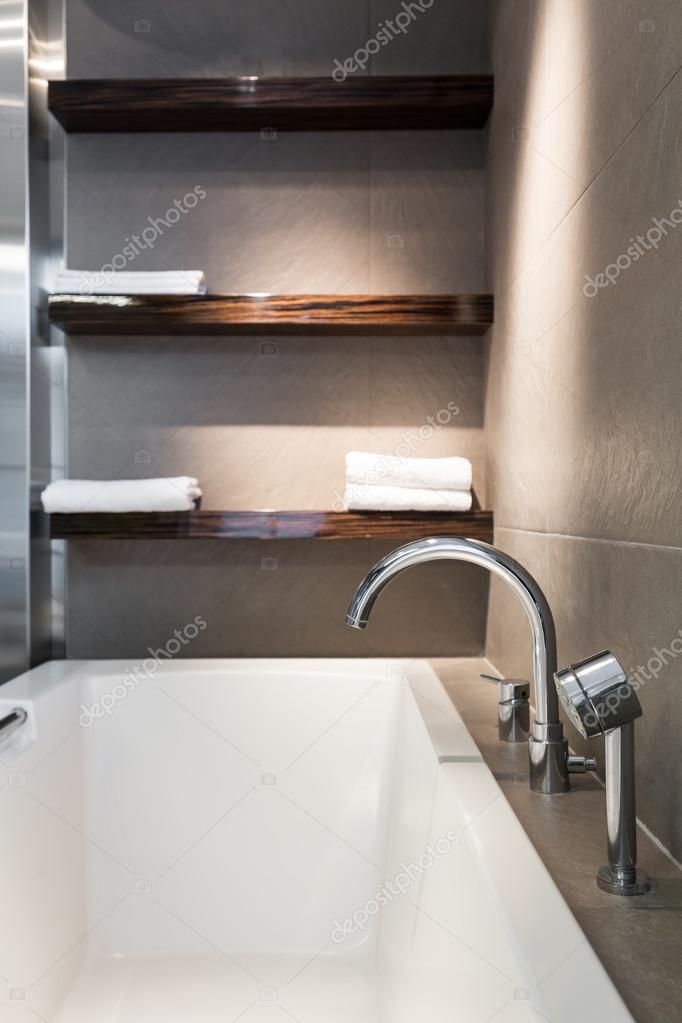 Bañera blanca grande y estantes de madera colgado en una pared — Foto de  photographee.eu 7677e324d360