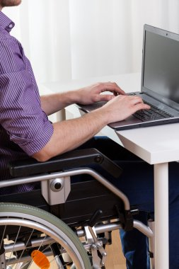Disabled man typing on notebook