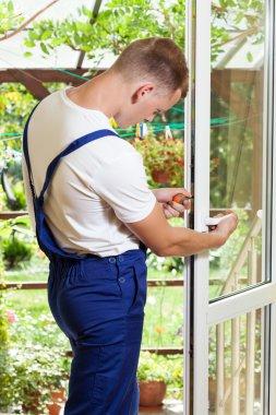 Handyman adjusting a window handle