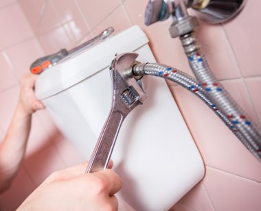 Plumber fixing toilet with wrench
