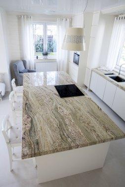 Big granitic worktop in bright kitchen
