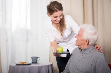 Helpful nurse and smiling pensioner