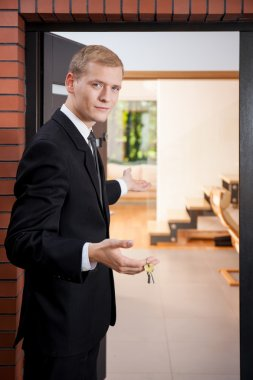 Handsome estate agent in the apartment