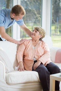 Male nurse assisting retired woman
