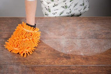 Woman cleaning dusty table