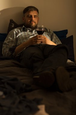 Single man in bed with wine