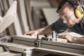 Mladý muž dělá ze dřeva