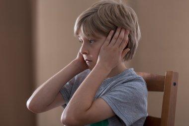 Sad boy plugging ears