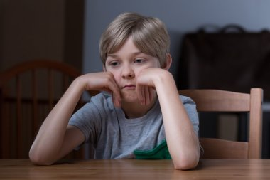Dissatisfied kid sitting at table