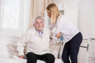 Care assistant helping senior man