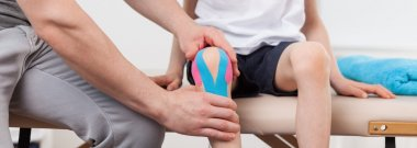 Physiotherapist applying kinesiology tapes