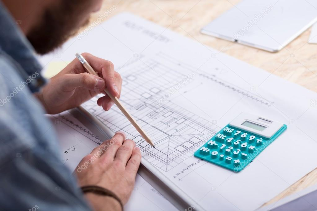 Architect estimating project cost stock photo photographee architect with blueprint and calculator estimating project cost photo by photographee malvernweather Gallery