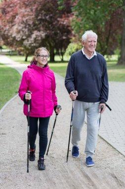 Elderly couple doing nordic walking