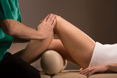 Massage therapist stroking female legs