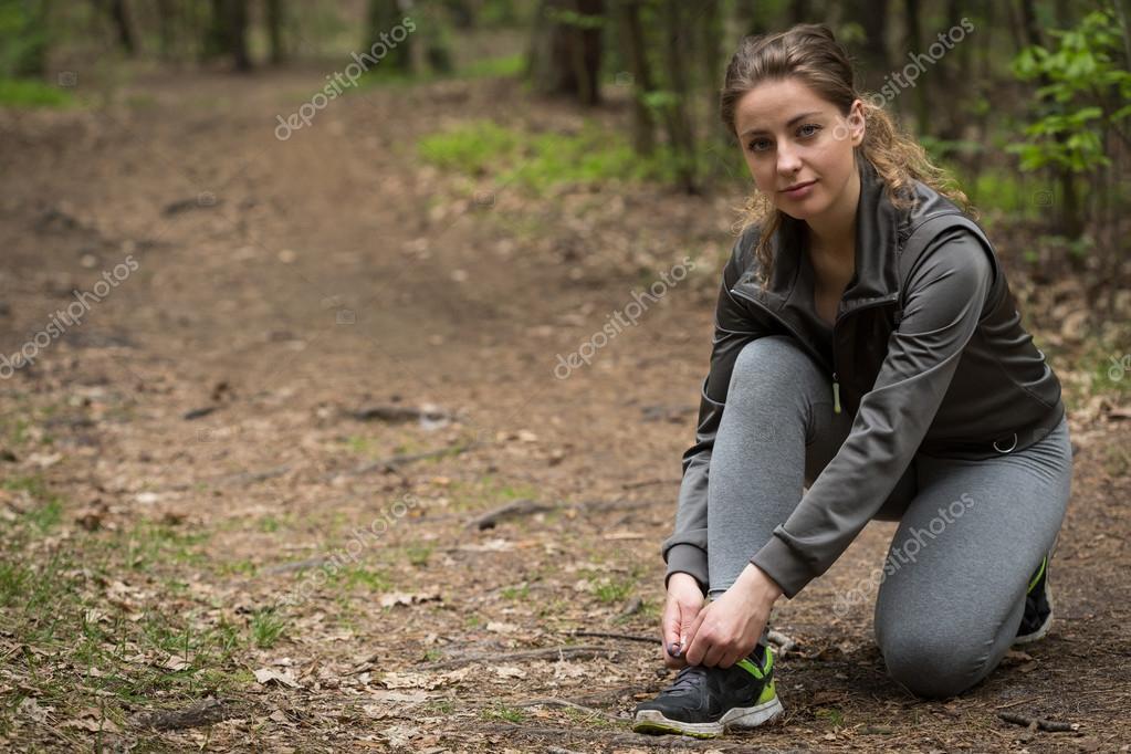 Runner in sportswear tying shoes