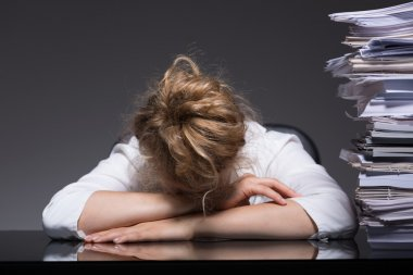 Overworked woman sleeping at workplace