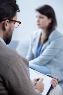 Male psychotherapist talking with woman