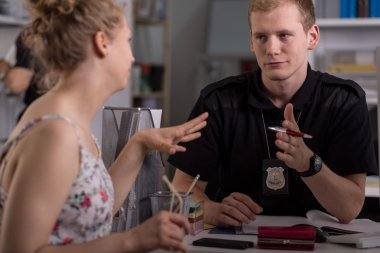 Police officer interrogating woman