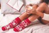 Žena v zimě ponožky s šálkem čaje