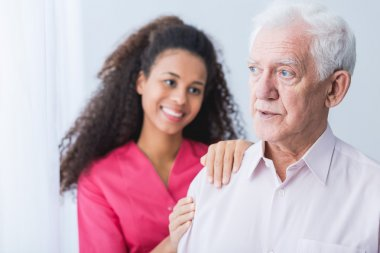 Female carer assisting senior man