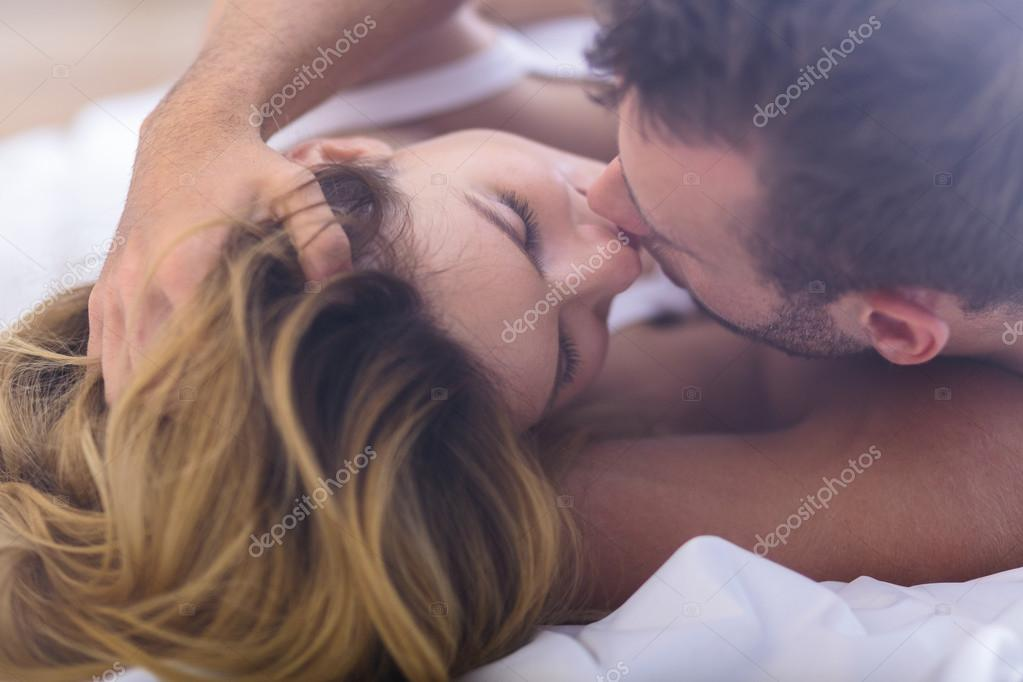 Married couple kissing in bed