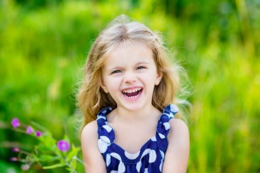 Fanny and beautiful laughing little girl with long curly hair