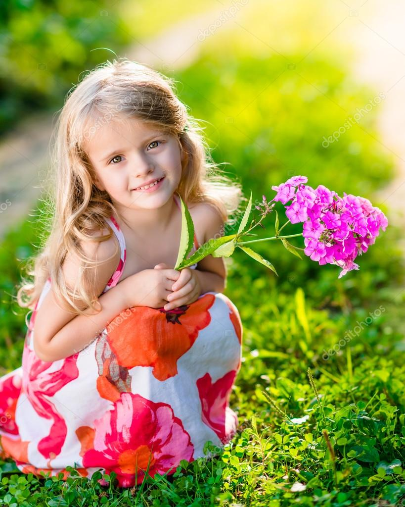 Smiling Pretty Little Girl Squatting And Holding Purple Flower In