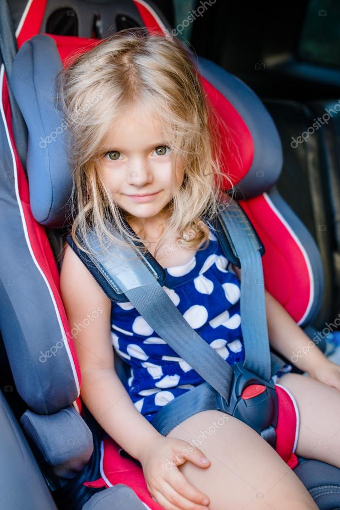 Adorable smiling little girl with long blond hair buckled in car ...