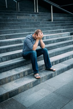 Despaired young man covering his face with hands sitting on stairs of big building. Feelings of sadness, despair and tragedy