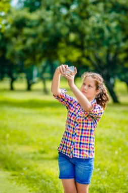Lovely teenage girl taking picture with smartphone in sunny day in summer park. Teenage girl taking selfie with smartphone