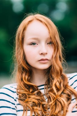 A beautiful girl with green eyes and long curly red hair in summer park. Outdoor portrait of a red-haired teenage girl. Adorable young redhead longhaired woman