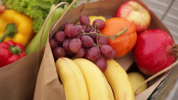 Potraviny ze supermarketu ve venkovním vozíku. Dodávka jídla během karantény. Cruft papírové eko tašky na nákupy. Čerstvé ovoce a zelenina, vegan