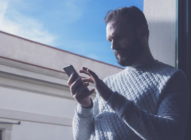 Portrait bearded man touching screen mobile phone. Man using contemporary smartphone, blue sky background. Horizontal, film effect