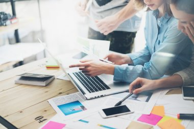 Creative team coworking project.Photo business managers working with new startup in modern loft.Analyze reports,plans. Notebook on wood table, papers, documents, statistics. Horizontal, blurred