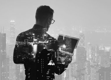 Double exposure young bearded businessman wearing black shirt and holding modern notebook hands. Panoramic view contemporary night city background. Black, white. Horizontal mockup