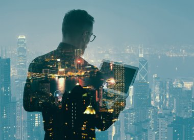 Double exposure young bearded businessman wearing black shirt and holding modern notebook hands. Panoramic view contemporary night city background. Horizontal mockup, bokeh, color