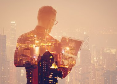 Double exposure young bearded businessman wearing black shirt and holding modern notebook hands. Panoramic view contemporary night city background. Horizontal mockup