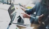 Setkání týmu bankéři. Fotografie mladých obchodní posádka s nový projekt při spuštění. Kreativní myšlenka diskuse. Notebook na dřevěný stůl. Idea prezentace, analýza marketingové plány. Rozmazané, filmový efekt.