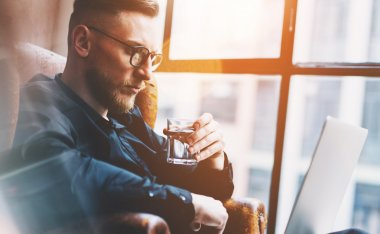 Closeup photo bearded businessman working on modern loft office. Man sitting in vintage chair, holding glass water. Using contemporary notebook, panoramic windows background. Horizontal, film effect.