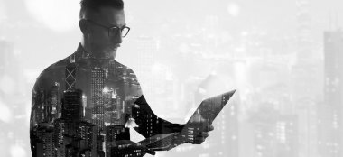 Double exposure bearded businessman wearing black shirt and glasses.Banker holding contemporary notebook hands,work online banking. Modern skyscraper city background. Wide mockup