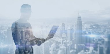 Double exposure photo bearded businessman wearing black shirt and glasses.Banker holding contemporary notebook hands,work online banking.Panoramic view modern skyscraper city background.Soft light