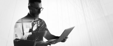 Double exposure bearded businessman wearing shirt and glasses,holding contemporary notebook hands. Portrait young banker using laptop in modern office, skyscraper background. Wide, black,white