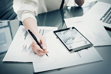 Investment manager working process.Photo woman work reports modern tablet screen.Statistics graphics screen.Private banker using pen for signs documents. New business project startup. Horizontal