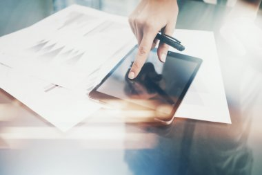 Photo woman working modern tablet,touching black blank screen. Finance investment work process.Banker holding pen for signs documents,markets reports on the table.Horizontal.Film and bokeh effects