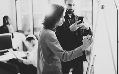 Creative managers meeting. Photo art director working with colleague designer new startup project. Idea, analyze marketing plans. Blurred background, light effects, film effect. Wide, black and white